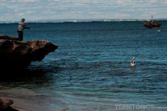 Pescador e pelicano de olho no peixe