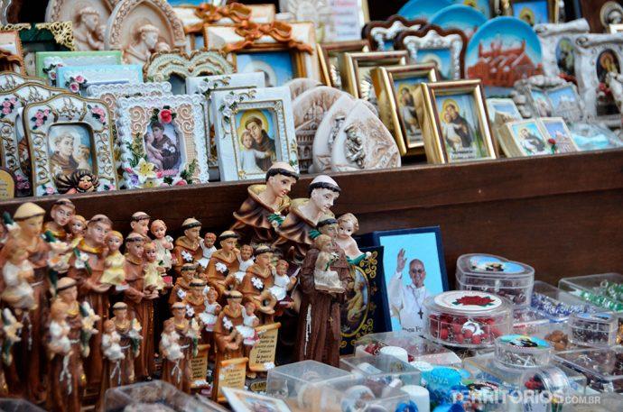 Santinhos e souvenires são vendidos em barracas em frente à igreja
