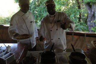 Cozinheiro e ajudante preparando o café da manhã na hora