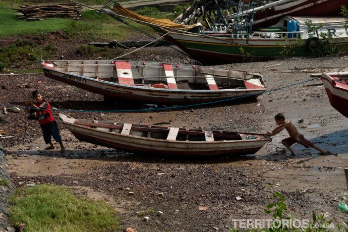 Crianças tentando desencalhar o barco