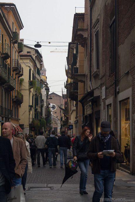 Rua estreita e com comércio em Verona