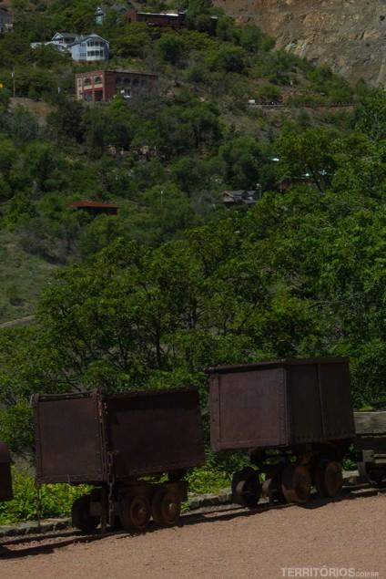 Carrinhos antigos e casas espalhadas na vegetação