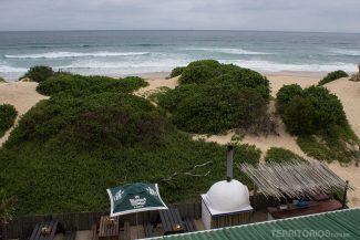 Vista da varanda para a praia com a pizzaria abaixo