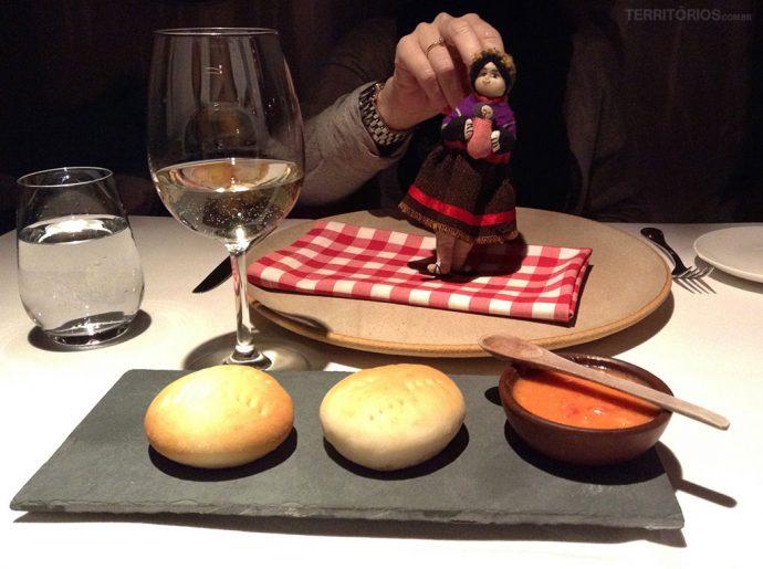 Boneca andina enfeita mesa do jantar e um dos pães especialidade da casa