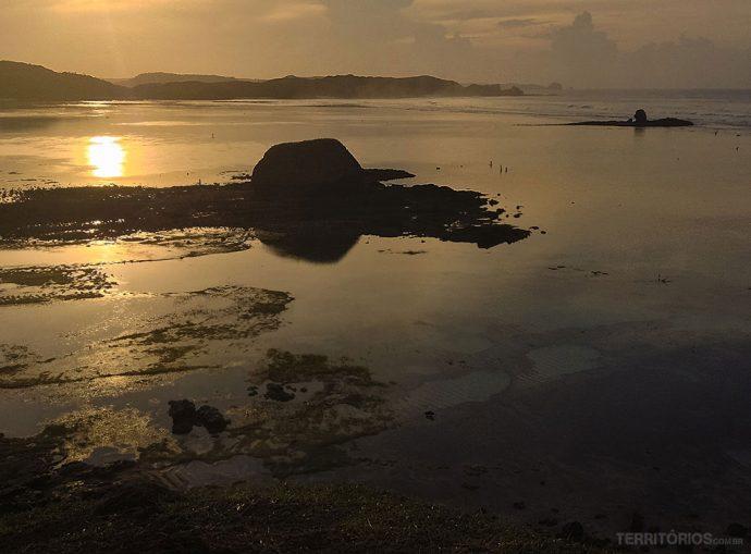 Nascer do sol nublado com pescadores aproveitando a maré baixa