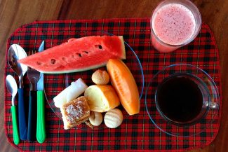 Frutas, pães e sucos no café da manhã
