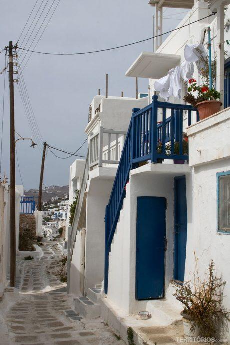 Casas brancas com portas, janelas e varandas de madeira em outra cor é o estilo arquitetônico em Myconos