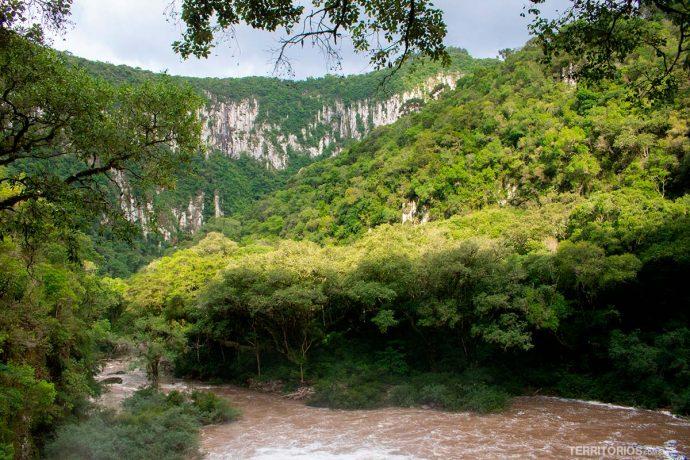 Rio com águas turvas e paredão de pedra com muito verde em Boqueirão do Leão, um dos destaques do Caminho das Cascatas