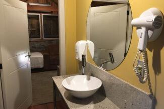 No corredor da suíte, pia e secador de cabelo para o hóspede